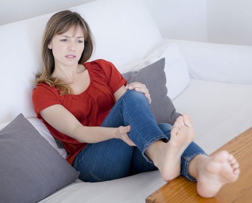 Woman wincing as she stretches her leg
