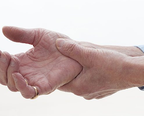 Old woman clutching sore arthritic hand