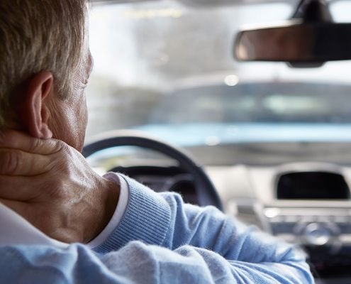Man behind the wheel of his car, grasping his neck in pain