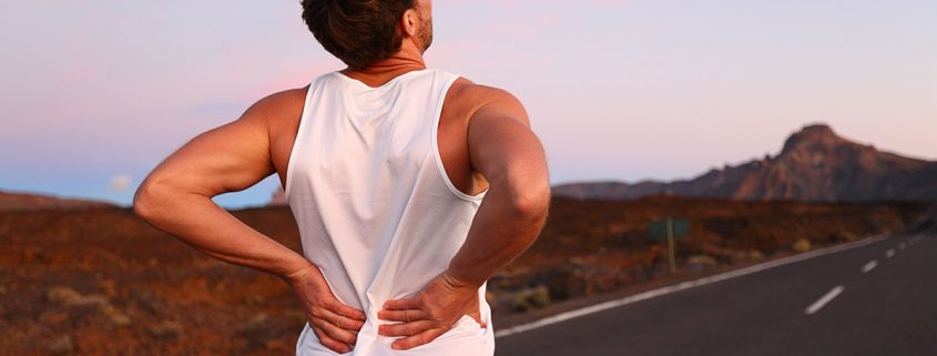 Runner grabbing his lower back with both hands, as if in pain