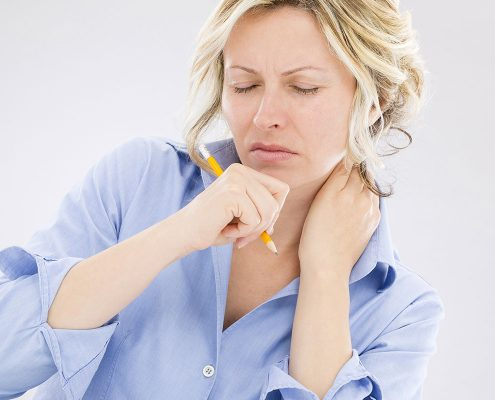 Woman scowling in pain and rubbing her neck