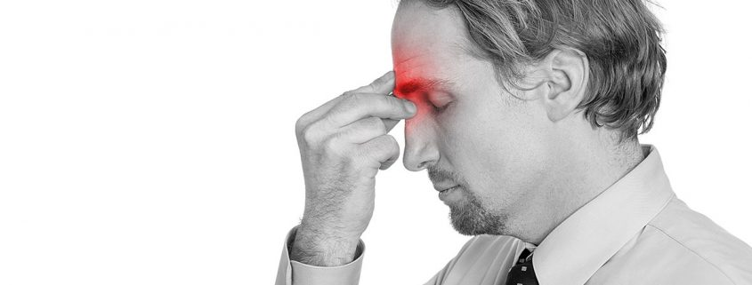 Man pinching the area between his eyes, as if his sinuses hurt