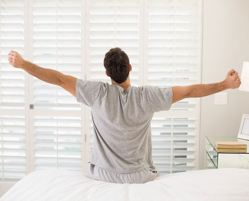 Man sitting on edge of bed, stretching, as if he's just woken up