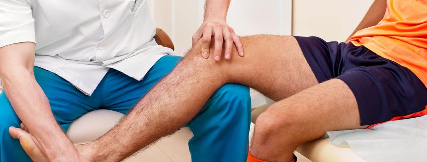Close-up of a doctor or therapist assessing the leg of an athlete