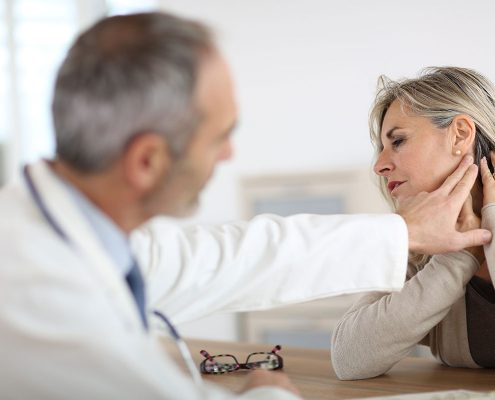 A woman showing her doctor where her neck pain is located