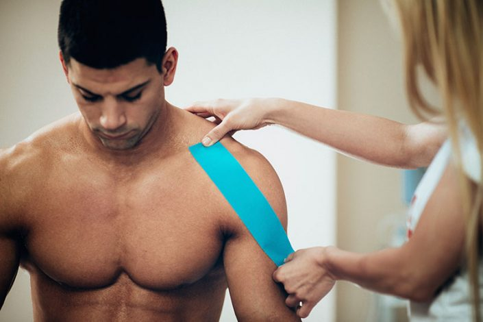 A female therapist applying sports tape to the shoulder of a male athlete