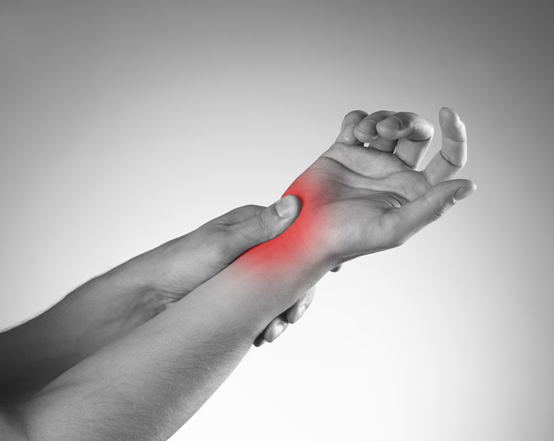 Close-up of a hand clutching a wrist, a red area added to indicate pain