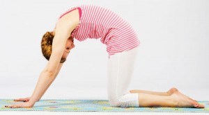 A woman in cat pose, on hands and knees with back arched and head down