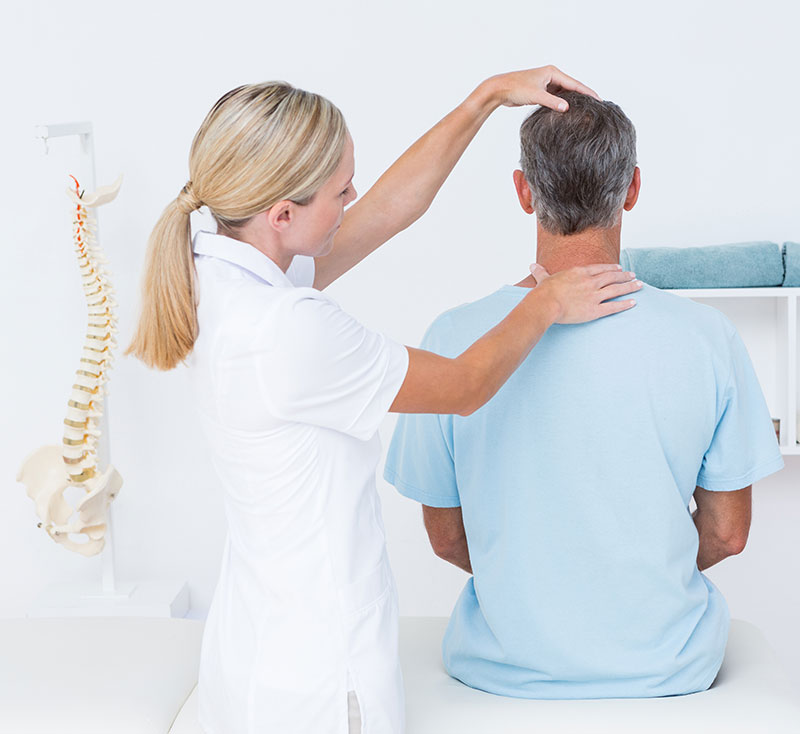 A female chiropractor assesses the spinal alignment of a male patient