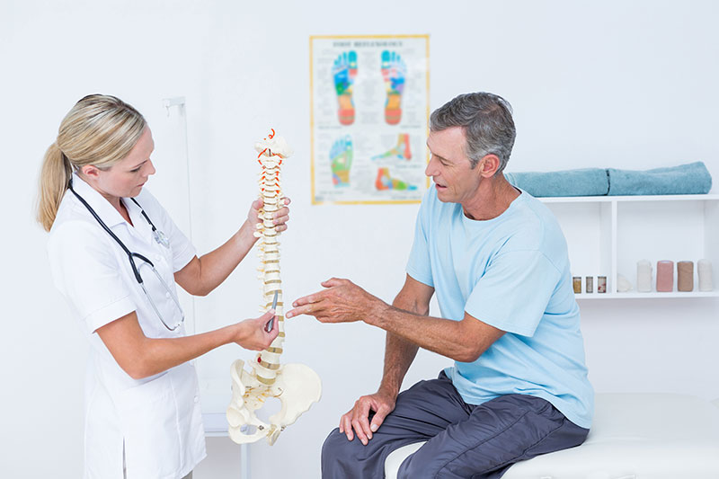 A male patient and a female medical professional consult a spinal diagram