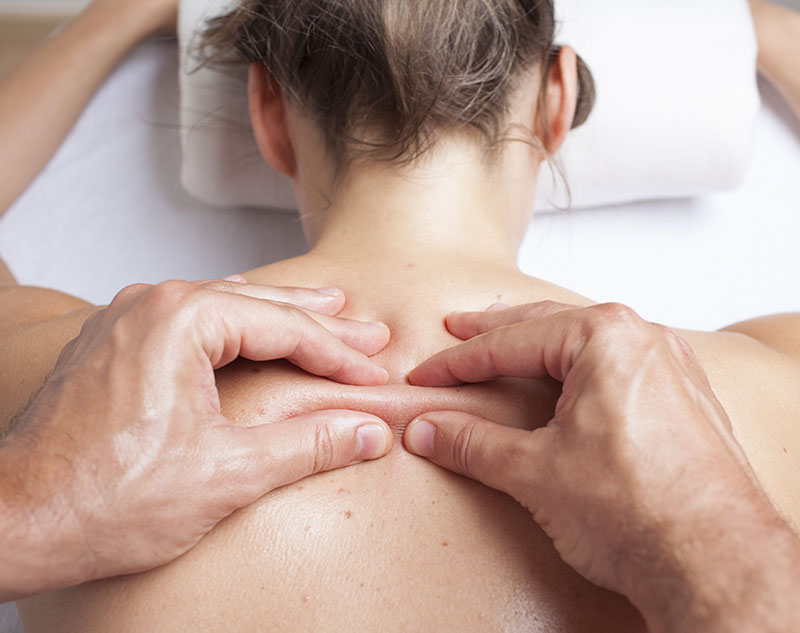 A woman receiving myofascial therapy on her back