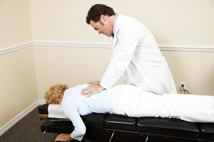 An older woman on a chiropractic table getting an adjustment from a male chiropractor