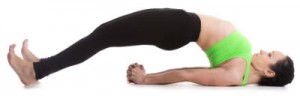 A woman in yoga gear lying on her back, legs and torso arched upward, arms under the body, hands clasped