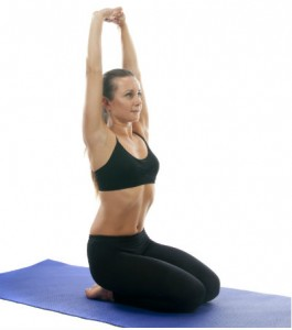 A woman in yoga clothes kneeling, torso upright, fingers interlaced and hands stretched up above the head