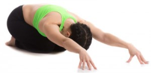 Woman in yoga gear in child's pose