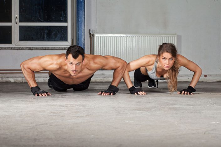 A well-muscled couple in workout gear doing planks