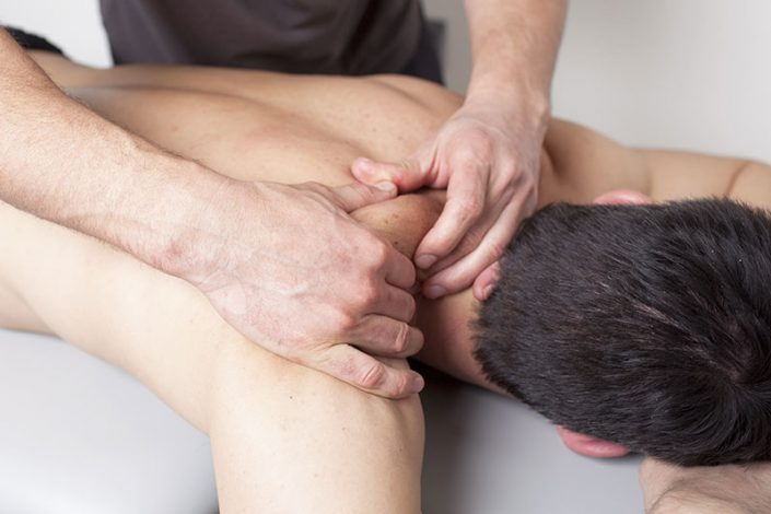 A close-up of a man having his shoulder massaged