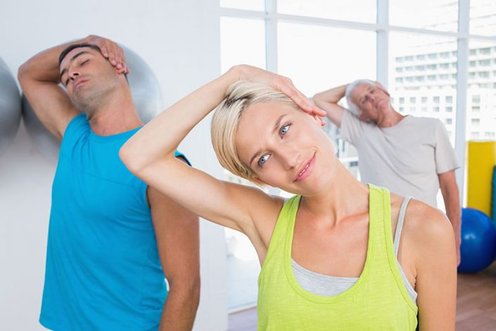 Three adults in an exercise class, performing a neck stretch
