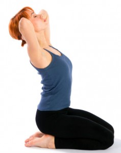 A woman in yoga gear on her knees, torso upright and stretching back a little, hands laced behind her head