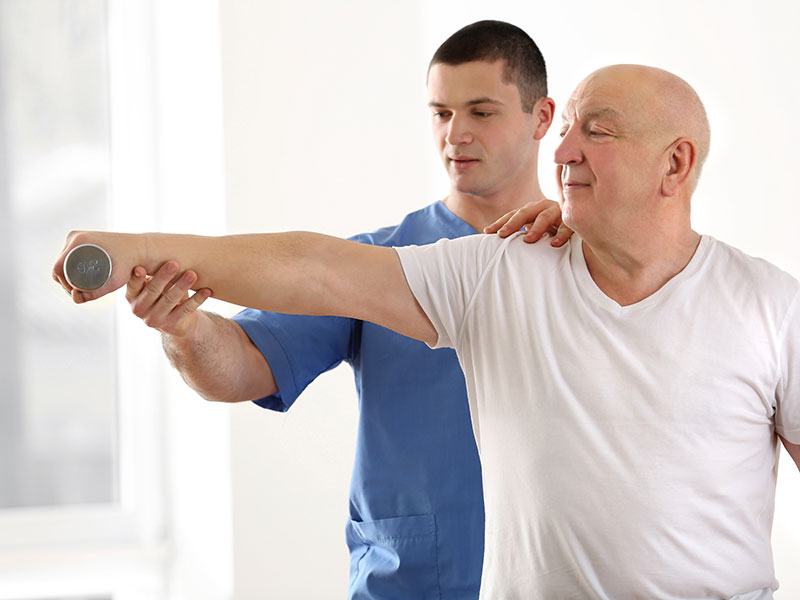 A physical therapist helps an elderly patient with strength exercises