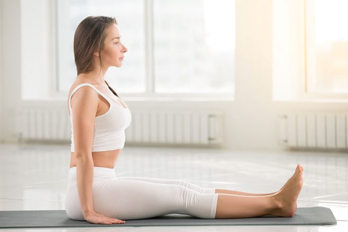 A woman sitting up straight on a yoga mat