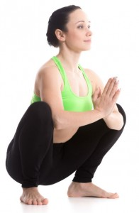 A woman in yoga gear squatting, hands palms together in front of chest