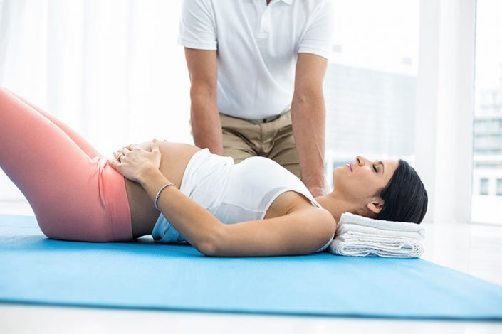 A pregnant woman lying on a yoga mat, a therapist in the background