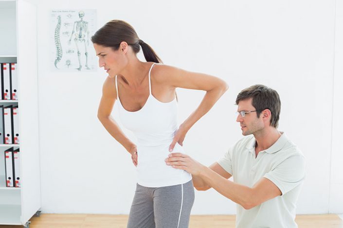 A woman wincing in pain as a male therapist examines her lower back