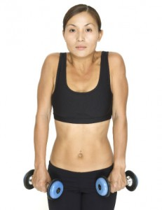 A woman holding dumbbells, her shoulders pulled up towards her ears