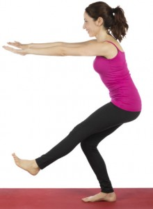 A woman in workout gear standing on her right foot, knee slightly bent, left leg straight, arms stretched forward