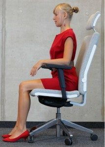 A woman dressed in business attire, sitting upright in a swivel chair