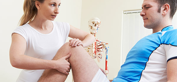 A female therapist working on the leg of a male athlete