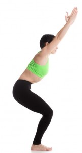 A woman in yoga gear in a half-seated position, arms stretched up