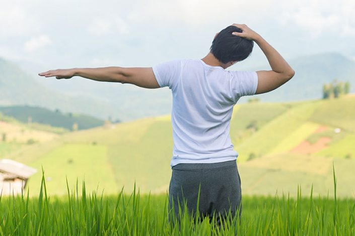Young man standing in a field of grass, performing a neck and shoulder stretch