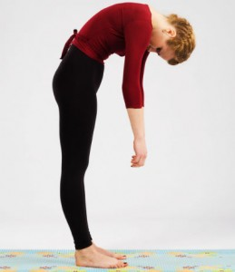 A woman in yoga gear standing, slightly bent over, head and arms dropped down