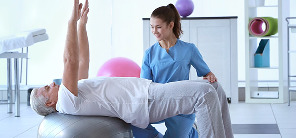 A female therapist working with an older man, who is lying back on an exercise ball, hands stretched into the air
