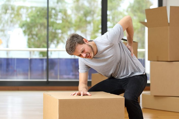 Young man moving boxes, bent over a box and grabbing his back in pain
