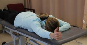 A woman lying face-down on a chiropractic table, right arm outstretched