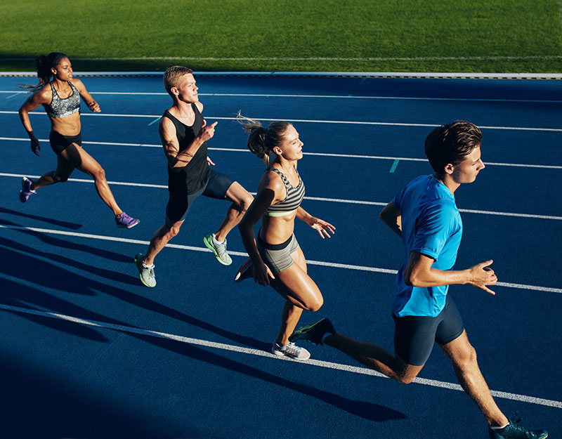A co-ed and multi-racial group of young athletes running on a track