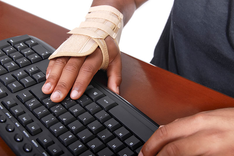 Close-up of a hand on a keyboard, a carpal tunnel brace on the wrist