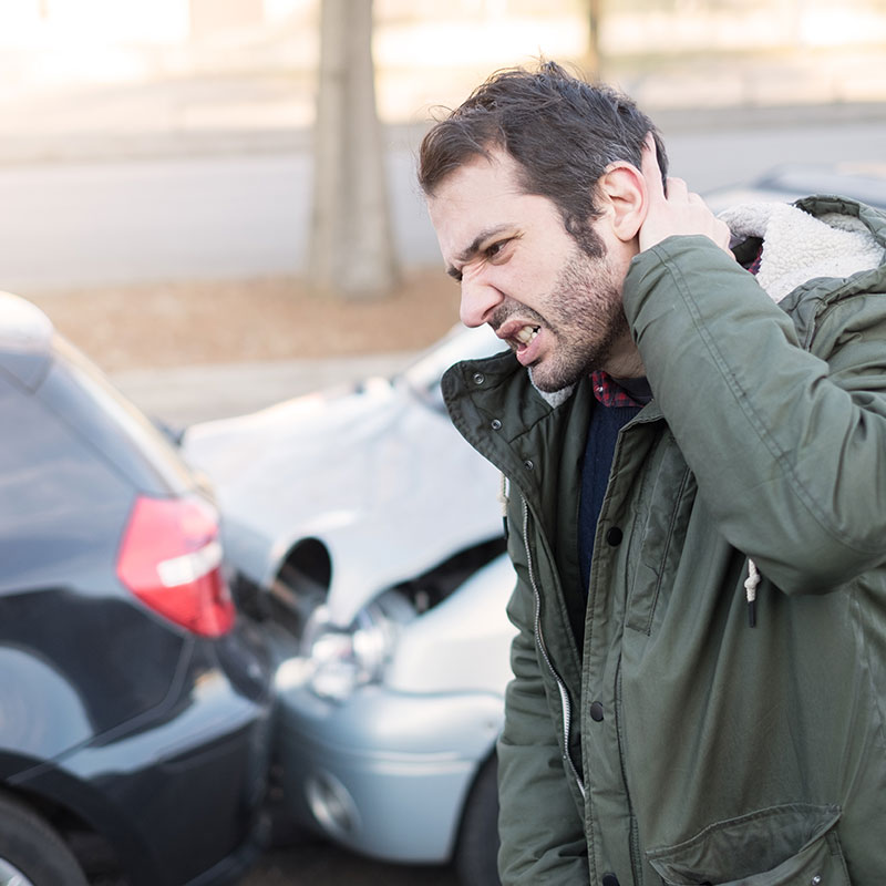 Man with whiplash cringing in pain, 2 smashed cars in the background