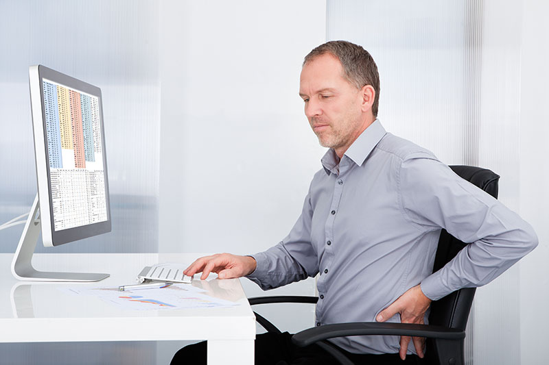 Man working at a desk, clutching his lower back as if it hurts