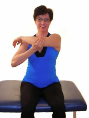 A woman sitting down, with her right hand pulling her left elbow across her chest