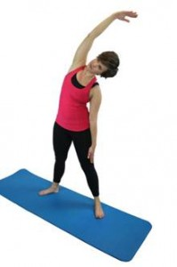 A woman in workout gear, performing a side bend with her right arm raised over her head and reaching left