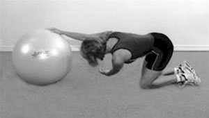 A woman, kneeling, with her right hand on an exercise ball and her left hand reaching underneath her right arm, in a trunk rotation stretch