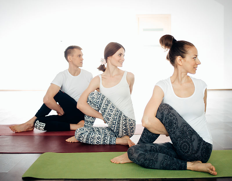 A trio of young adults in a yoga class